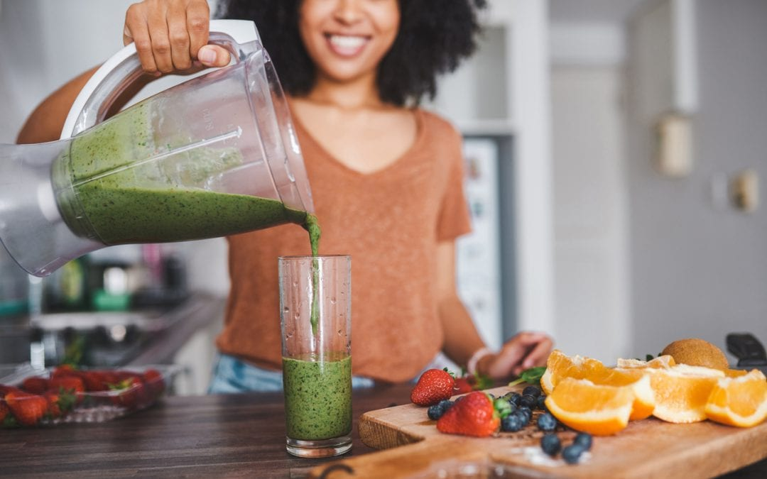 Shot of a young woman making a healthy smoothie at home