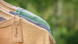 Organic,Clothes.,Natural,Colored,T-shirts,Hanging,On,Wooden,Hangers,In