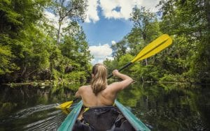 Woman kayaks in ecotourism destination