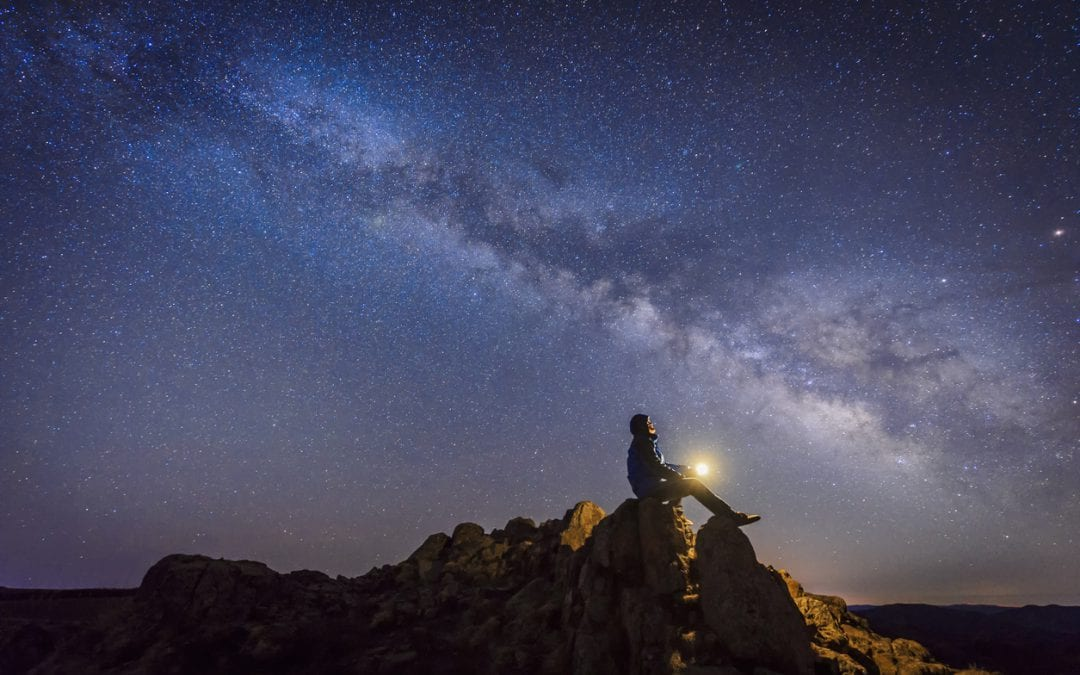 Man sitting under the Milky Way