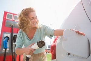 Woman plugging in electric vehicle shows need for green tech innovation
