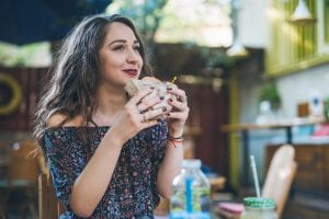 Woman enjoys plant-based burger from food service distributor