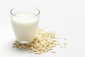Oat milk and rolled oats. Organic vegan non-dairy plant-based milk in a glass.