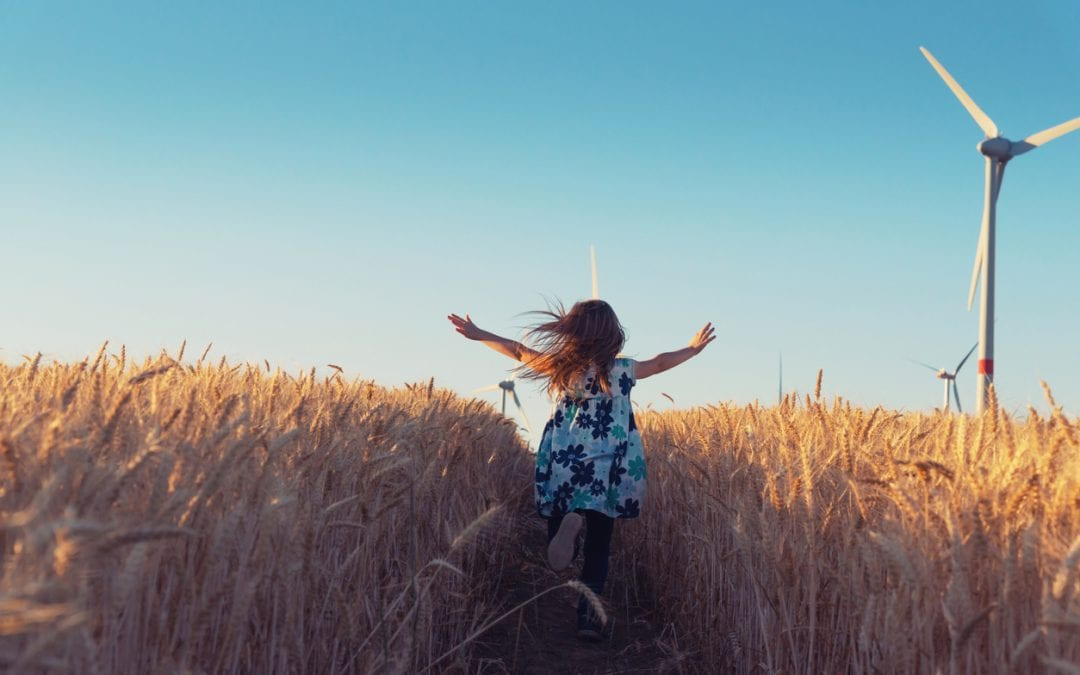 Girl running through field with sustainability windmills