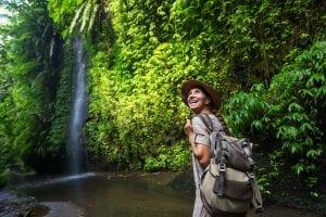 woman hiking in jungle near waterfall