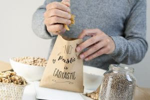 closeup of a man putting some dry macaroni on a brown paper bag, with the text no plastic is fantastic written in it, placed on an electronic scale